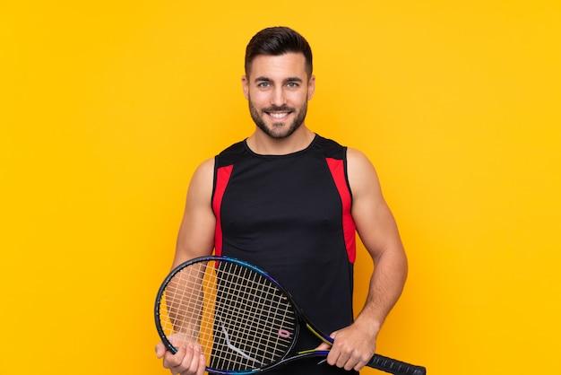Теннисист над изолированной желтой стеной много улыбается