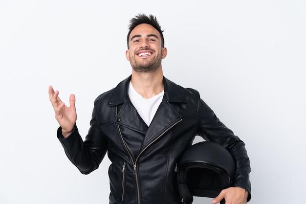 多くの笑みを浮かべてオートバイのヘルメットを持つ男