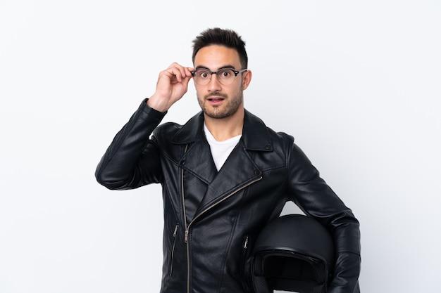 Человек с мотоциклетным шлемом в очках и удивлен