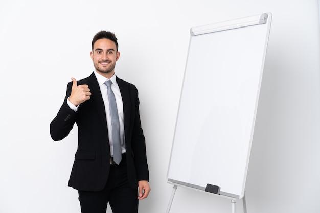 Молодой человек дает представление на белой доске и с большими пальцами руки вверх