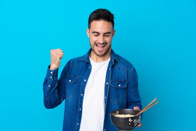 箸で麺のボウルを押しながら勝利を祝って孤立した青い壁の上の若いハンサムな男