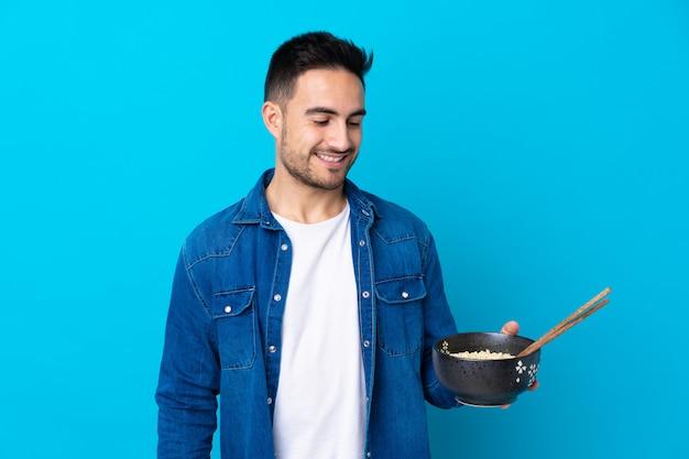 箸で麺のボウルを押しながら幸せな表情で孤立した青い壁の上の若いハンサムな男