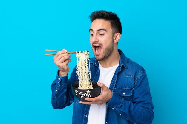 箸で麺のボウルを保持し、それを食べる分離の青い壁の上の若いハンサムな男