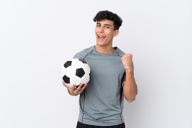 アルゼンチンのフットボール選手の男が勝利を祝って孤立した白い壁の上