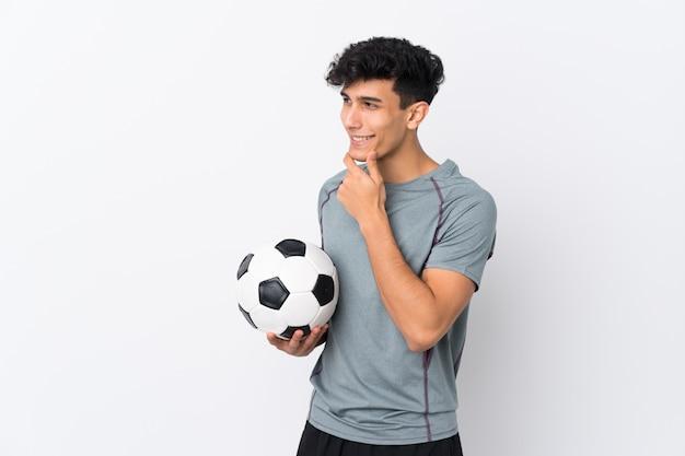 アルゼンチンのフットボール選手の男側を見ている分離の白い壁