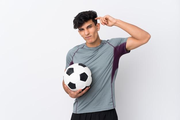 Аргентинский футболист человек над изолированной белой стеной с сомнениями и с выражением лица путать