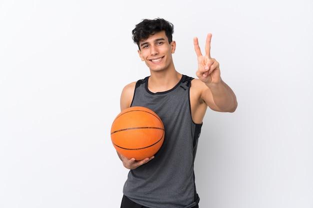 笑顔と勝利のサインを示す分離の白い壁の上のバスケットボール選手の男