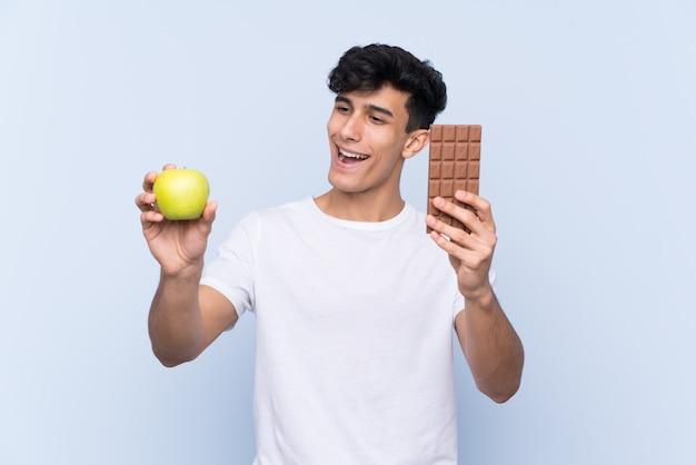 片方の手でチョコレートタブレットと他の手でリンゴを取って孤立した青い壁の上の若いアルゼンチン人