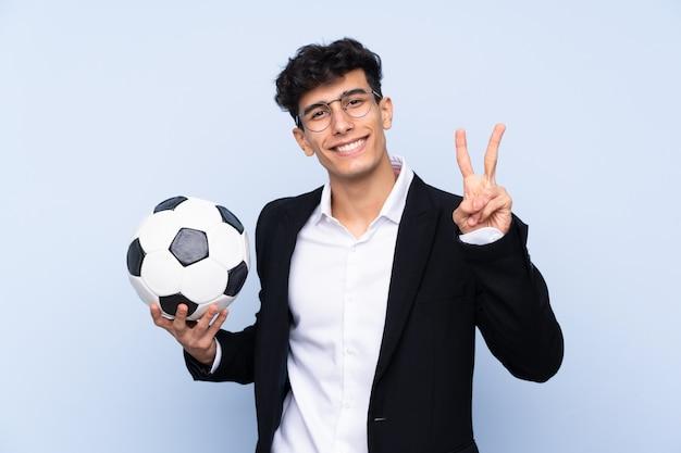 笑みを浮かべて、勝利のサインを示す分離の青い壁の上のアルゼンチンのサッカーのコーチ