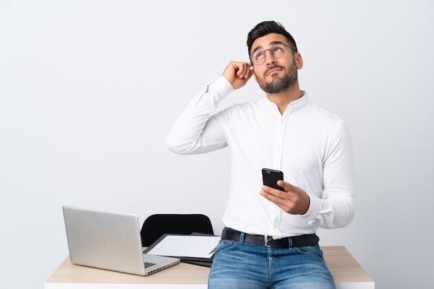 Молодой бизнесмен держит мобильный телефон, имея сомнения с выражением лица смутить