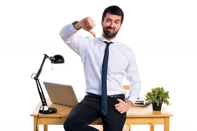 Бизнесмен в своем офисе делает плохой сигнал