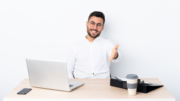 Молодой бизнесмен на рабочем месте, рукопожатие для закрытия хорошей сделки