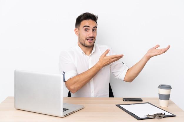 Молодой деловой человек с мобильным телефоном на рабочем месте, протягивая руки в сторону за приглашение прийти