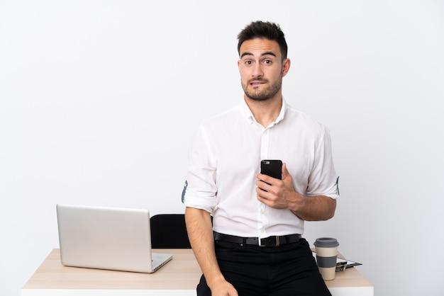 Молодой деловой человек с мобильным телефоном на рабочем месте, имея сомнения и с выражением лица путать