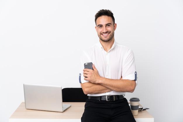 Молодой деловой человек с мобильным телефоном на рабочем месте аплодировал