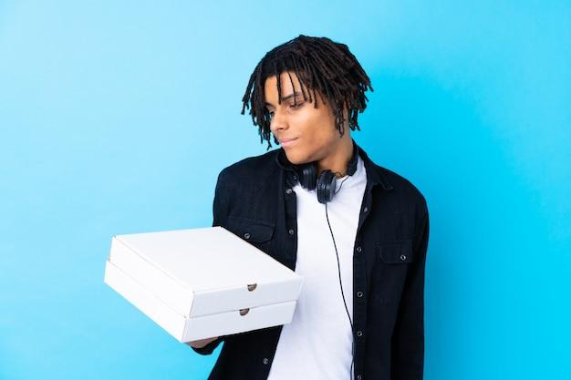 Молодой человек, держащий коробки для пиццы над изолированной стеной