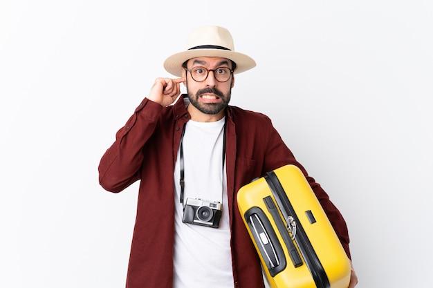 Человек путешественника с чемоданом над изолированной стеной