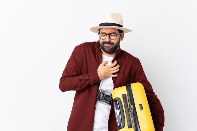 孤立した壁の上のスーツケースを持つ旅行者男