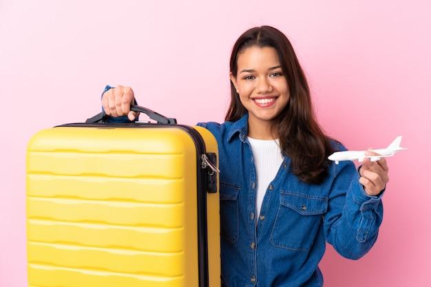孤立した壁を越えてスーツケースを持つ旅行者女性