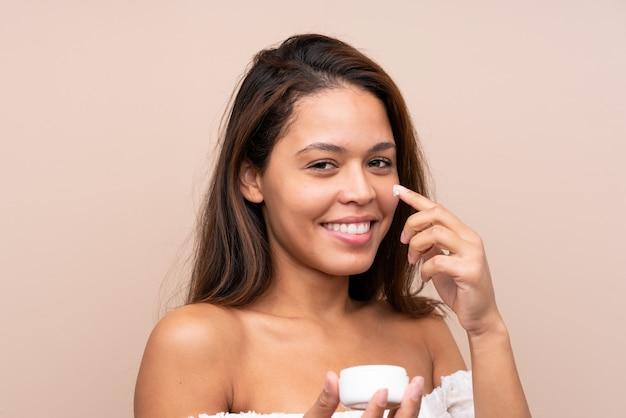 孤立した壁に化粧品を置く若いきれいな女性