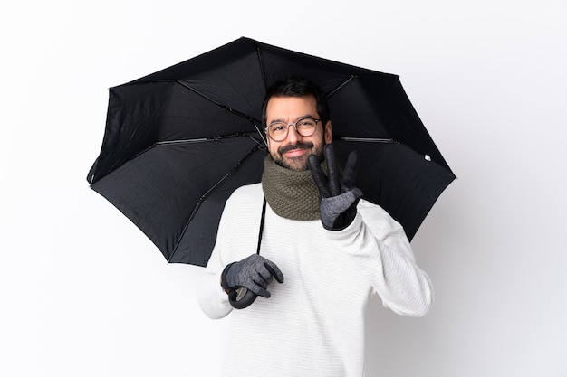 孤立した壁に傘を保持しているひげを持つ男