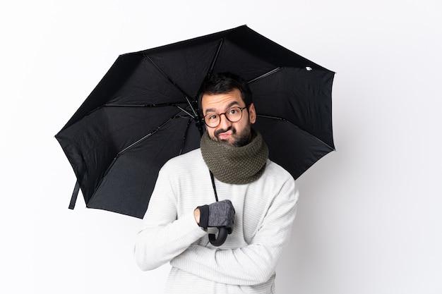Человек с бородой держит зонтик над изолированной стеной