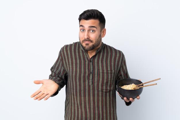 孤立した壁に麺のボウルを保持している若い男