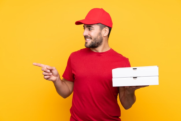 Мужчина держит коробки с пиццей на изолированной стене