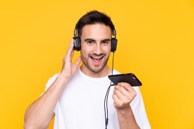 Человек с бородой слушает музыку через изолированную стену