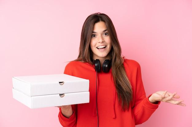 孤立した壁にピザの箱を置くティーンエイジャーの女の子