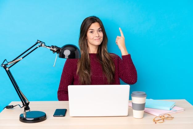 ノートパソコンで職場でティーンエイジャーの学生の女の子