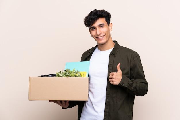 物でいっぱいの箱を拾いながら移動する男