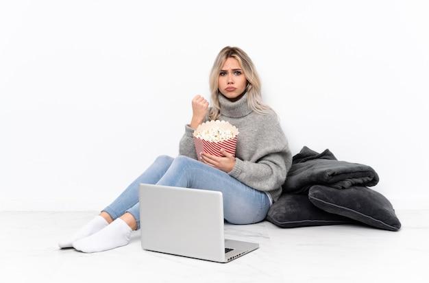 Блондинка подросток ест попкорн во время просмотра фильма на ноутбуке с сердитым жестом
