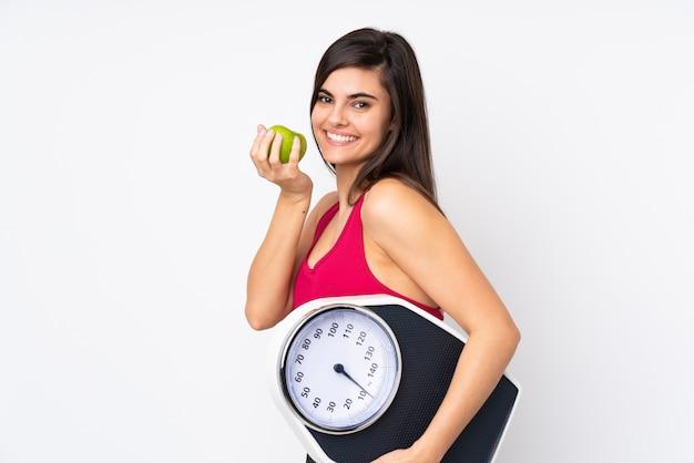 計量機とリンゴの孤立した白い壁の上の若い女性