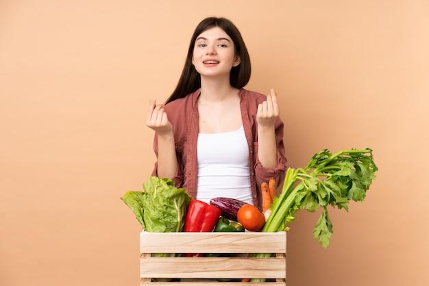 お金のジェスチャーを作るボックスで採れたての野菜を持つ若い農家の少女