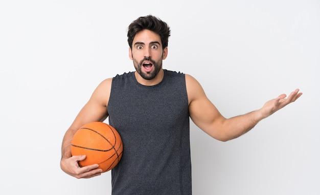 ショックを受けた表情で孤立した白い壁の上のひげを持つバスケットボールプレーヤー男