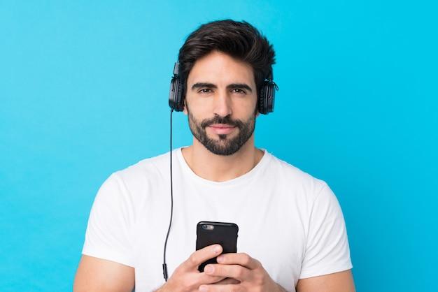 Молодой красивый человек с бородой над изолированной синей стеной прослушивания музыки с мобильного телефона и глядя спереди