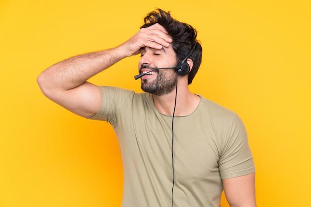 Телемаркетер человек, работающий с гарнитурой над желтой стене смеется
