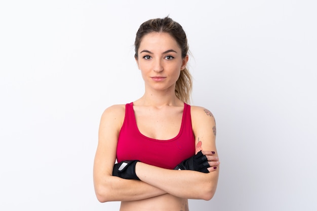 腕を組んで孤立した白い壁の上の若いスポーツ女性
