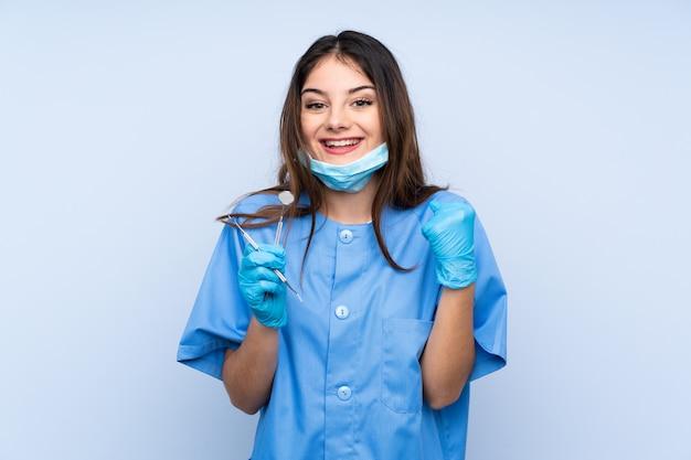 Инструменты удерживания дантиста женщины над изолированной голубой стеной празднуя победу
