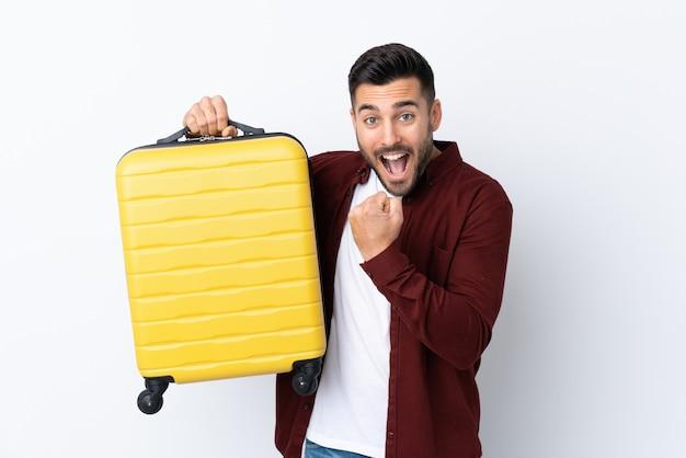 旅行スーツケースと休暇で孤立した白い壁の上の若いハンサムな男