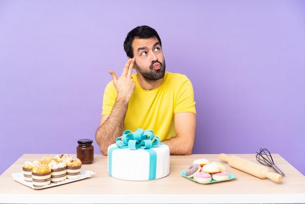 大きなケーキとテーブルの男