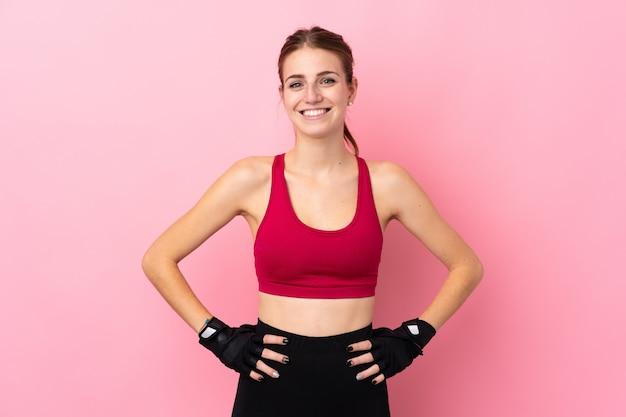 ヒップで腕でポーズと笑顔の分離のピンクの壁の上の若いスポーツ女性