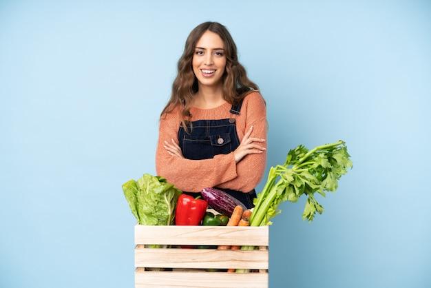 Фермер со свежесобранными овощами в коробке, держа руки скрещенными в переднем положении