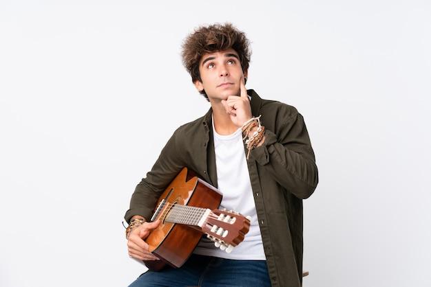 アイデアを考えて孤立した白い壁の上のギターを持つ若い白人男
