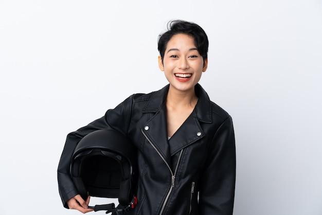 Молодая азиатская девушка с мотоциклетным шлемом над изолированной белой стеной с удивлением и шокированным выражением лица
