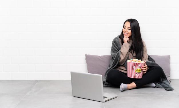 ポップコーンのボールを保持していると側にいるラップトップで映画を見せて若いコロンビアの女性