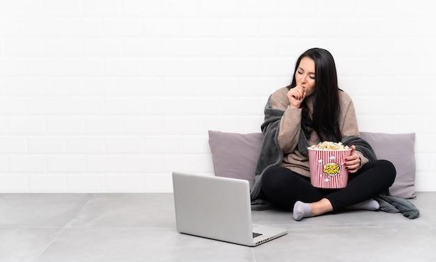 Молодая колумбийская женщина, держащая миску попкорна и показывающая фильм в ноутбуке, страдает от кашля и плохо себя чувствует