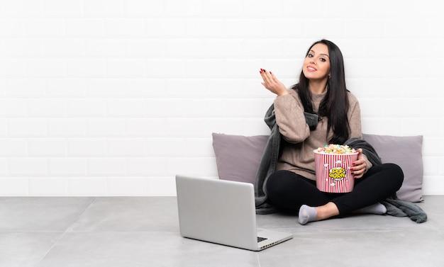 ポップコーンのボールを保持し、来て招待する側に手を伸ばすラップトップで映画を見せて若いコロンビアの女性