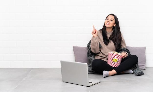 ポップコーンのボウルを保持し、最高の兆しを見せて指を持ち上げてノートパソコンで映画を見せて若いコロンビアの女性